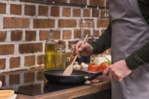 Mann bereitet Essen in Pfanne zu