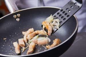 Koch bereitet Essen in Pfanne zu