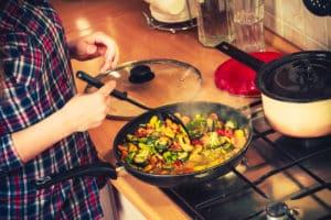 Mann bereitet Gemüsepfanne vor