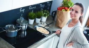 Frau bereitet Crêpes zu