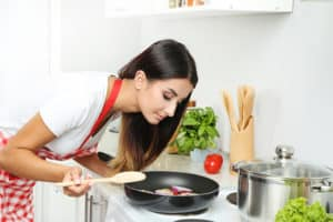 Junge Frau kocht in Küche