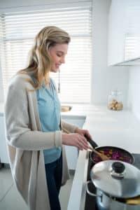 Frau bereitet Essen in Pfanne zu