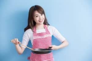 Hausfrau mit Bratpfanne in den Händen