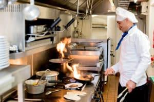 Koch bereitet in Großküche Speisen zu