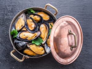 Muscheln in Kupferpfanne zubereiten