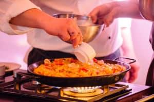 Koch bereitet Paella vor